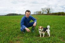 Portrait of farmer crouching in field with dog — Stock Photo