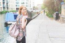 Mulher por canal olhando sobre o ombro na câmera sorrindo, Londres, Reino Unido — Fotografia de Stock