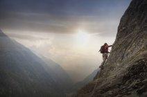 Escalade sur une paroi rocheuse au-dessus d'une vallée, Alpes, Canton de Berne, Suisse — Photo de stock