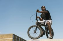 Young man on BMX bicycle looking over his shoulder in skatepark — Stock Photo