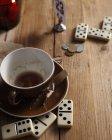 Copo de café vazio e dominó na mesa de madeira — Fotografia de Stock