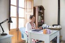 Зрілі жінки, набравши на ноутбуці офіс в майстерні мило ручної роботи — стокове фото
