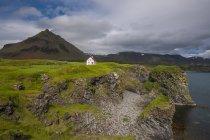 Cottage building on green hills landscape — Stock Photo
