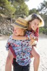 Man on beach giving smiling woman piggyback, Majorca, Spain — Stock Photo