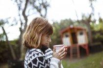 Жінка в саду проведення кава з футболу — стокове фото