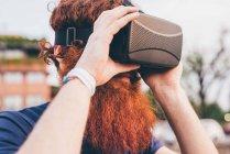 Hipster hombre joven con pelo rojo y la barba con casco de realidad virtual - foto de stock