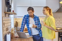 Couple using laptop and having coffee in kitchen — Stock Photo