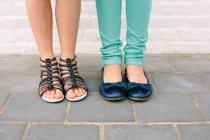 Крупним планом дві сестри ноги і взуття — стокове фото