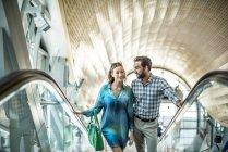 Tourist couple moving up shopping mall escalator, Dubai, United Arab Emirates — Stock Photo