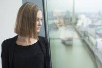 Молодая деловая женщина смотрит в окно офиса — стоковое фото