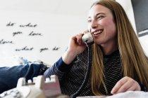 Взрослая женщина лежит на кровати и разговаривает по стационарному телефону. — стоковое фото