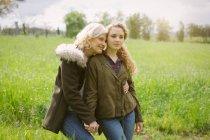 Ritratto di madre e figlia adolescente che tengono le mani nel campo — Foto stock