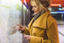Woman pointing at street map in underground station — Stock Photo