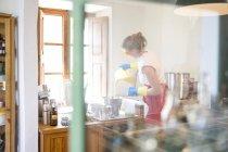 Junge Frau strömenden Flüssigkeit Lavendel Seife in Schüssel in handgemachte Seife Werkstatt — Stockfoto