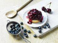Ягоди Губка десерт на пластину з свіжих вишень і Чорниця — стокове фото