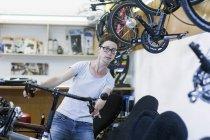 Жінка в майстерню з ремонту велосипедів перевірка кермо на лежачому велосипеді — Stock Photo
