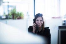 Молодая женщина в офисе по телефону смотрит в камеру улыбаясь — стоковое фото