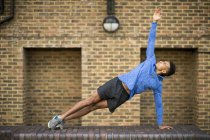 Man stretching in front of brick wall, Wapping, London, UK — Stock Photo
