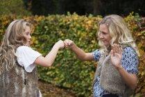 Dos hermanas haciendo golpes de puño por seto de jardín - foto de stock