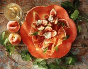 Plate parma ham with figs and soft cheese on table — Stock Photo