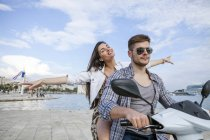 Coppia giovane che cavalca ciclomotore al porto, Split, Dalmazia, Croazia — Foto stock
