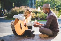 Couple learning to play guitar in park — Stock Photo