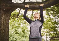 Young woman doing pull ups on park tree branch — Stock Photo