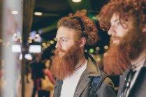 Junge männliche Hipster Zwillinge mit dem roten Haar und Bärte Schaufensterbummel in der Nacht — Stockfoto