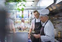 Chefs reading order in traditional Italian restaurant kitchen — Stock Photo
