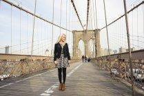 Retrato do turista feminino parado na ponte de Brooklyn, Nova Iorque, EUA — Fotografia de Stock