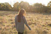 Молода жінка, проходячи через поле в осінь, задній вид — стокове фото
