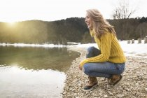Mid adult woman crouching beside lake, smiling, German Alps, Germany — Stock Photo
