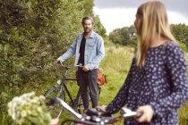 Mujer ciclista volviendo a novio en camino rural - foto de stock