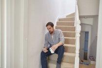 Hombre adulto medio sentado en la escalera leyendo textos de teléfonos inteligentes - foto de stock