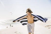 Boy on beach arms open holding towel looking at camera smiling — Stock Photo