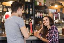 Молодая пара, разговор в баре — стоковое фото
