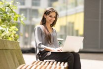 Businesswoman typing on laptop on park bench, London, UK — Stock Photo