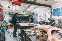 Two metalworkers working at forge workbench — Stock Photo