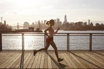 Side view of woman jogging on pier, Manhattan, New York, USA — Stock Photo