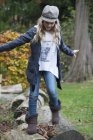 Girl stepping over logs in park — Stock Photo