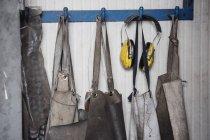 Avental de carpinteiro suspenso sucessivamente em ganchos — Fotografia de Stock