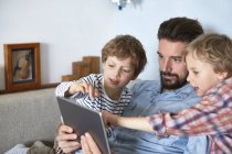 Father and sons on sofa using digital tablet — Stock Photo
