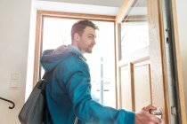 Man leaving front door of house and looking at camera — Stock Photo