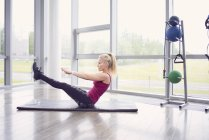 Woman working out on yoga mat in gym — Stock Photo