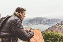 Jeune homme à l'affût de la terrasse du lac de Côme, Italie brumeux — Photo de stock