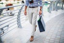 Vue de la taille vers le bas du jeune homme se promenant sur le front de mer portant un sac à provisions, Dubaï, Émirats arabes unis — Photo de stock