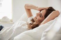 Vista del nivel de la superficie de la hermosa mujer joven recostada en la cama - foto de stock