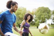 Молодая футбольная пара, играющая дерзко в парке — стоковое фото
