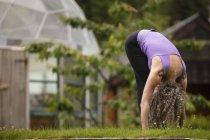 Зрілі жінки, практикуючи вперед рази йога в eco lodge саду — стокове фото
