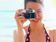 Молодая женщина с камерой на пляже — стоковое фото